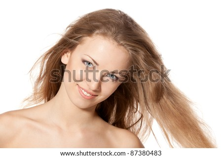 Close up portrait of smiling beautiful blond female with hair lightly fluttering in the wind over white background