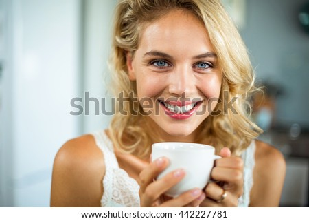 Close-up portrait of smiling beautiful woman holding coffee cup at home