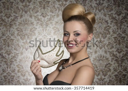 close-up portrait of smiling beautiful woman with creative elegant hair-style, cute make-up and stylish necklace taking cute decorated mask in the hand and looking in camera  - stock photo