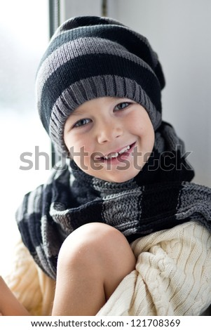 Close-up portrait of smiling boy wearing knitted hat - stock photo