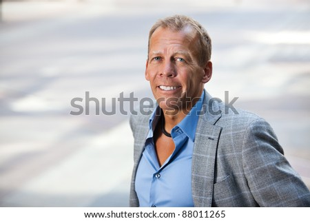 Close-up portrait of smiling businessman - stock photo