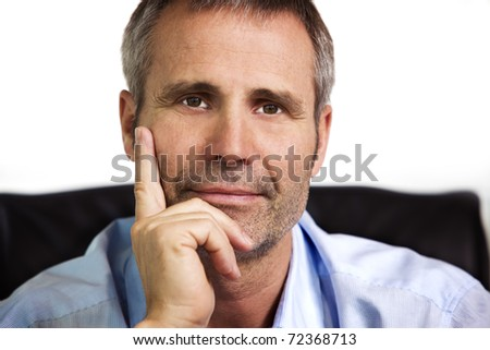 Close up portrait of smiling businessman in blue shirt looking straight and resting chin on  hand, isolated on white background. - stock photo