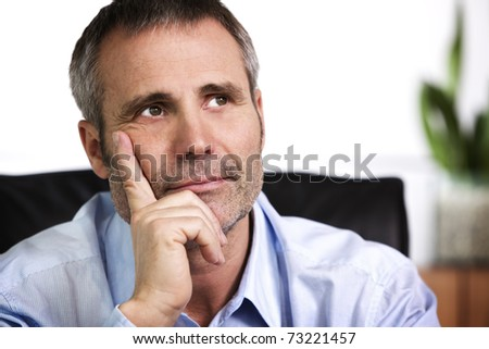 Close up portrait of smiling businessman in blue shirt looking up and resting chin on  hand, isolated on white background. - stock photo