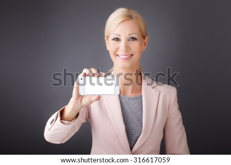 Close-up portrait of smiling businesswoman holding hand a mobile phone with blank screen. Isolated on grey background.