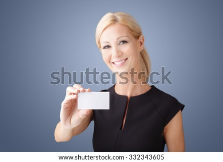 Close-up portrait of smiling businesswoman holding in her hand a mobile phone with blank screen while standing at isolated background.