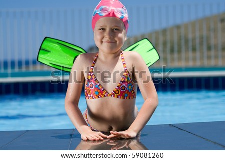 Close-up portrait of smiling cute little child in bathing cap, glasses and fins is lying on the swimming pool ledge - stock photo