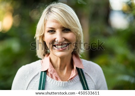 Close-up portrait of smiling female gardener at greenhouse