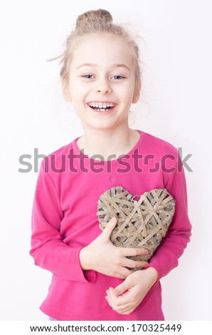 Close up portrait of smiling five years old caucasian blond child girl holding heart symbol on a white background. Love, Valentine's Day or happy childhood concept. - stock photo