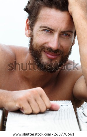 Close up Portrait of Smiling Handsome Man with No Shirt Posing at the Sea  - stock photo