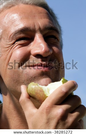 Close-up portrait of smiling man eating pear - stock photo