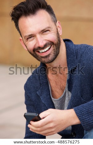 Close up portrait of smiling man sitting outdoors with mobile phone
