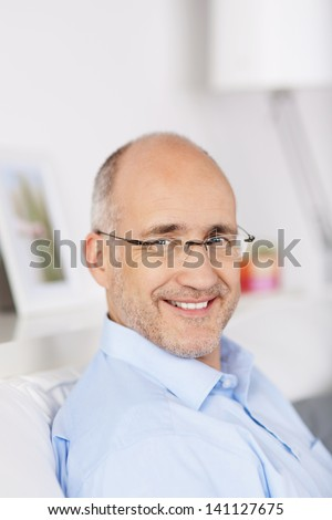 Close up portrait of smiling mature man indoors - stock photo