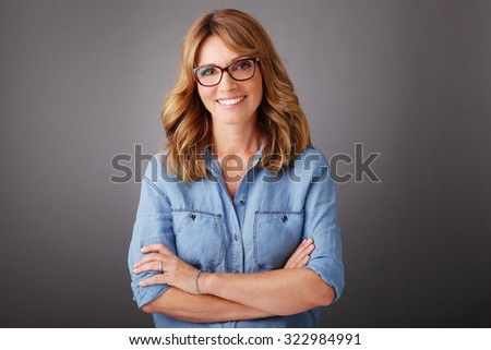 Close-up portrait of smiling middle age businesswoman with arms crossed standing at isolated background.