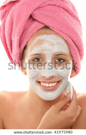 Close-up portrait of smiling teenage girl removing facial mask