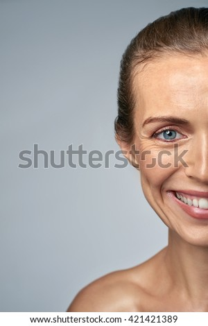Close up portrait of smiling woman in her 30s, showing fine wrinkles and aging - stock photo