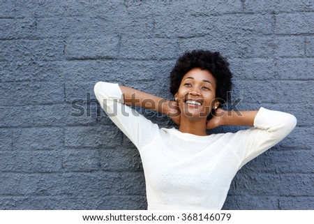 Close up portrait of smiling young african woman looking away against gray wall - stock photo