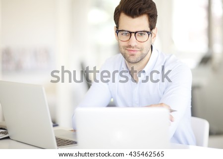 Close-up portrait of smiling young creative professional man working on laptops while sitting at his workstation.