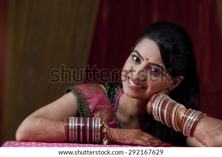 Close-up portrait of smiling young Indian bride - stock photo