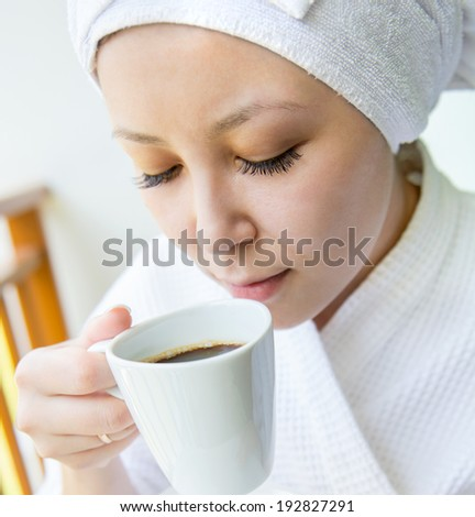 Close-up  portrait of Smiling Young woman in the towel hat  with the cap of coffee at home