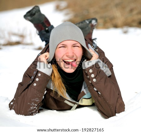 Close-up portrait of smiling young woman lying on a snow indicate the language and holding hands to her head. The concept photo winter recreation, healthy lifestyle , happy people - stock photo