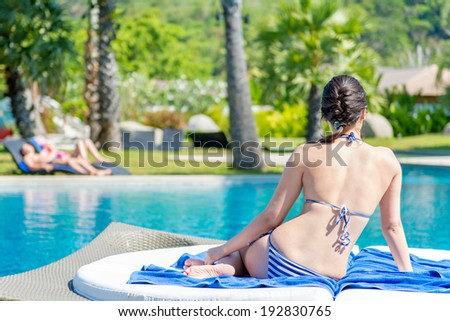 Close-up portrait of smiling young woman siting sun lounger  outdoor against a pool - stock photo