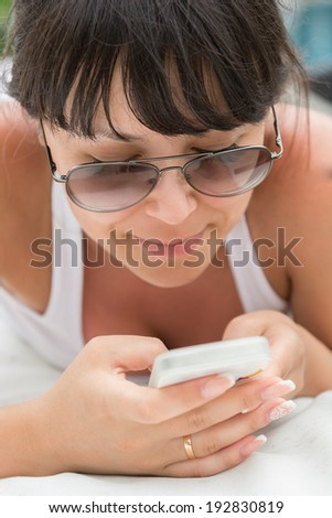 Close-up portrait of smiling young woman to lie  outdoor with telephone  - stock photo