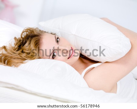 Close-up portrait of smiling young woman with pillow relaxing - indoors - stock photo