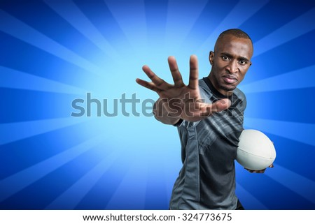 Close-up portrait of sportsman gesturing while standing with rugby ball against blue background - stock photo