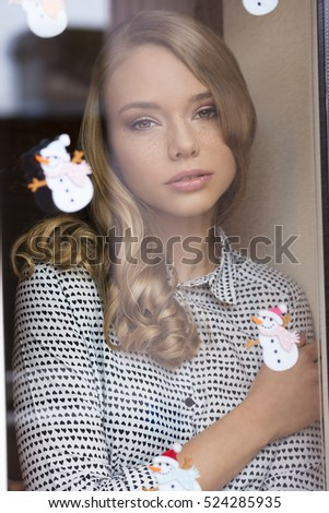 close-up portrait of stunning blonde woman with freckles on visage and lovely style posing behind window pane decorated with small snowman stickers. She is looking in camera with romantic eyes
