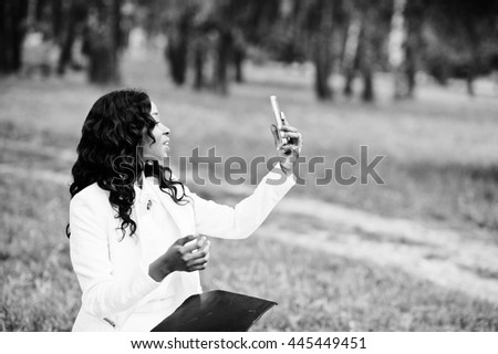 Close up portrait of stylish black african american girl taking selfie with pink mobile phone - stock photo