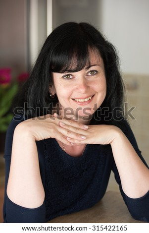 Close up portrait of successful business woman resting her chin on her hands and looking directly at the camera in the kitchen