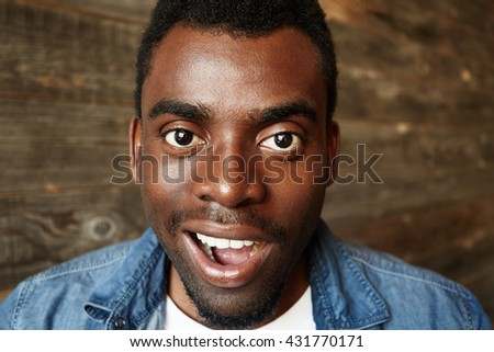 Close up portrait of successful young black entrepreneur wearing denim shirt looking and smiling at the camera with winning happy expression, achieving life goals. Success and achievement concept - stock photo