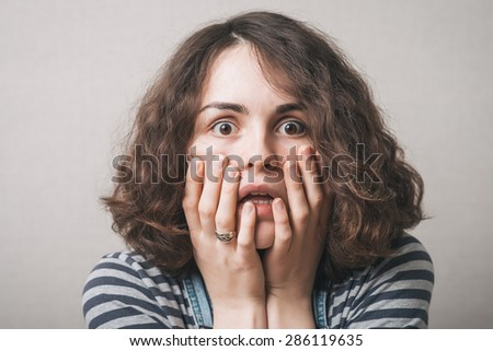 Close-up portrait of surprised beautiful girl holding her head in amazement  - stock photo