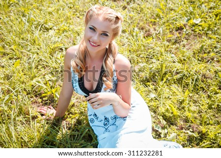 Close-up portrait of sweet young pretty blonde girl with colored make-up. Summer, outside