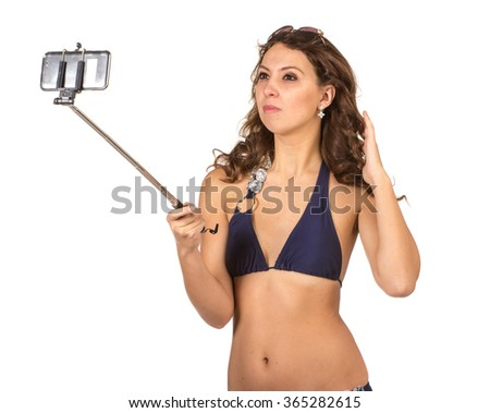 Close up portrait of Tanned adult woman in blue bikini swimsuit taking herself photo with big smatphone on stick