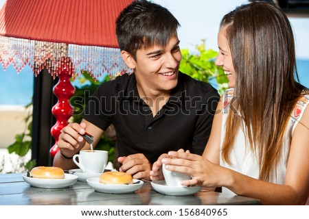 Close up portrait of teen couple enjoying breakfast in restaurant. - stock photo