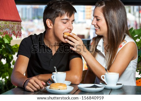 Close up portrait of teen couple fooling around in coffee bar. - stock photo