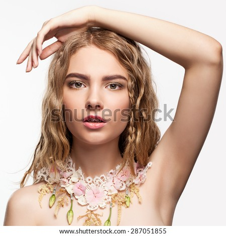 Close-up portrait of teen girl with flower necklace and hand on head - stock photo