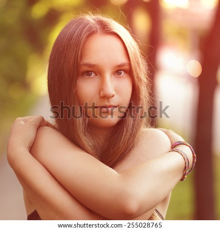 close up portrait of teen girl with naked shoulders in sunset light - stock photo
