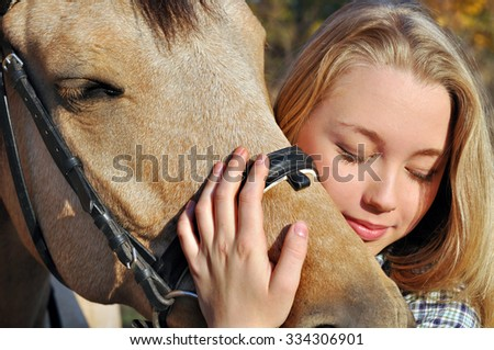 close-up portrait of teenage girl and horse  - stock photo