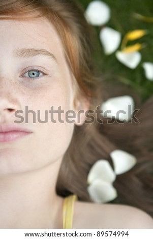 Close up portrait of teenage girl laying down on grass and petals. - stock photo