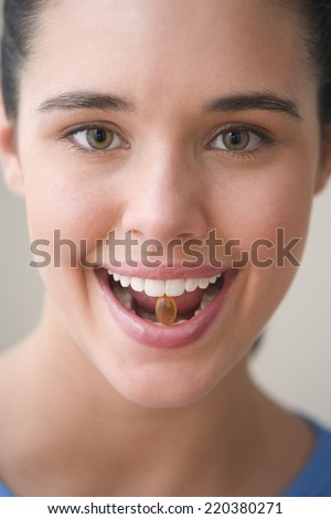 Close up portrait of teenager with vitamin between teeth - stock photo