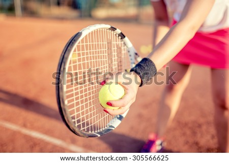 close up portrait of tennis racquet with fitness girl. healthy training for sportswoman details - stock photo