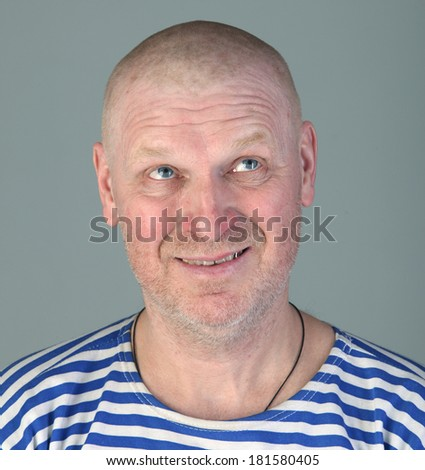 close-up portrait of the adult bald white man in a striped vest with a blissful view looking up studio