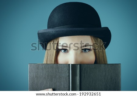 Close-up portrait of the elegant girl model in bowler hat reading a book. Refined style of old Europe. - stock photo