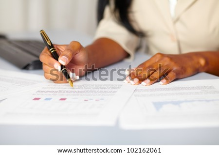 Close up portrait of the hands of a young professional working on documents - stock photo