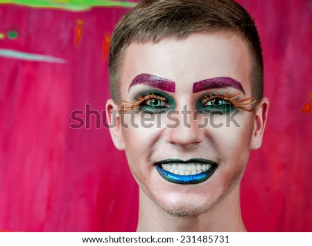 Close-up portrait of the handsome young man fashion model with make-up and big eyelashes - stock photo