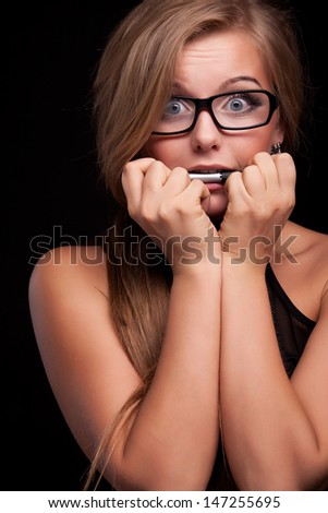 Close-up portrait of the scared woman in black glasses, isolated on black - stock photo