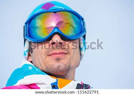 Close up portrait of the ski goggles of a man with the reflection of snowed mountains - stock photo