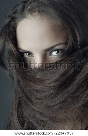 Close-up portrait of the woman face covered by her hairs - stock photo